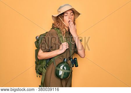 Young blonde explorer woman with blue eyes hiking wearing backpack and water canteen bored yawning tired covering mouth with hand. Restless and sleepiness.
