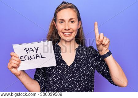 Young beautiful blonde woman holding paper with pay equal protest text smiling with an idea or question pointing finger with happy face, number one