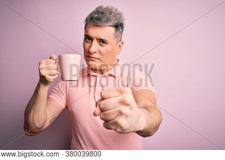 Young modern handsome man drinking a cup of hot coffee over isolated pink background annoyed and frustrated shouting with anger, crazy and yelling with raised hand, anger concept
