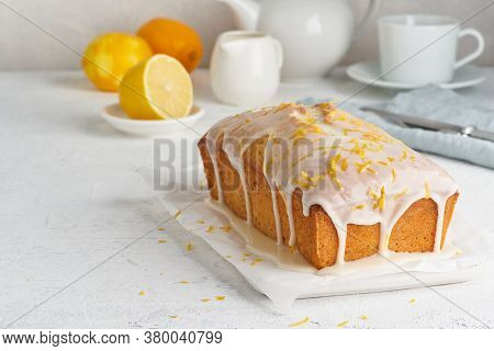 Lemon Bread Coated With Sugar Sweet Icing. Whole Loaf. White Background, Side View, Copy Space