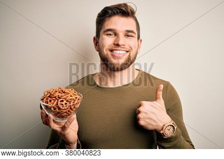 Young blond German man with beard and blue eyes holding bowl with baked pretzel happy with big smile doing ok sign, thumb up with fingers, excellent sign