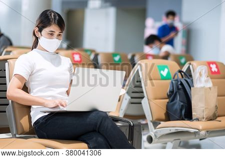 Young Female Wearing Face Mask And Using Computer Laptop In Airport, Protection Coronavirus Disease