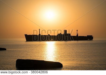 Beautiful Landscape By The Sea, At Sunrise. The Silhouette Of A Shipwreck. Golden Colors