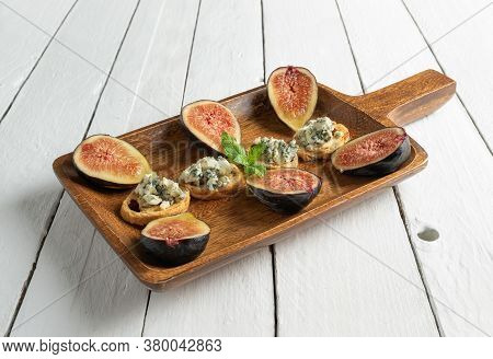 Toasts With Roquefort Cheese And Fresh Figs, On A Wooden Serving Board, On White Wood Background