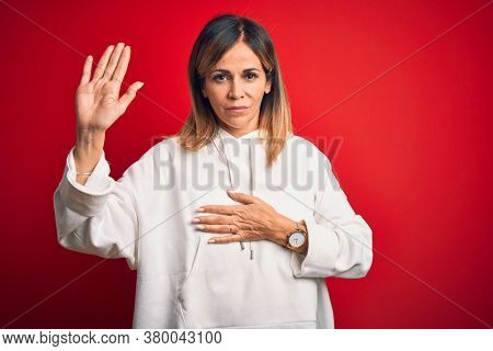 Middle age beautiful sportswoman wearing casual sweatshirt over isolated red background Swearing with hand on chest and open palm, making a loyalty promise oath