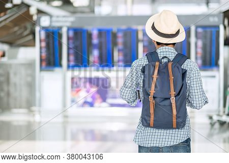Young Man Traveler With Hipster Backpack Checking Flight Time, Asian Passenger With Hat Looking To I