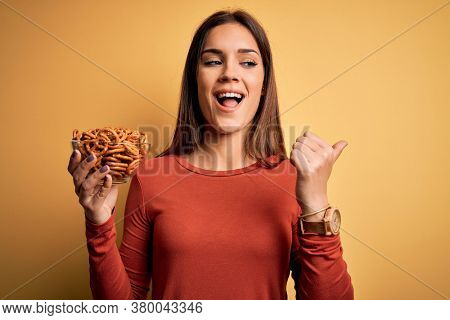 Young beautiful brunette woman holding bowl with germany baked pretzels pointing and showing with thumb up to the side with happy face smiling