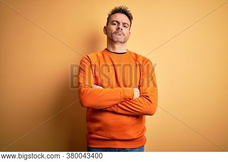 Young handsome man wearing orange casual sweater standing over isolated yellow background skeptic and nervous, disapproving expression on face with crossed arms. Negative person.