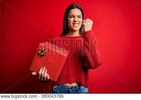 Young beautiful brunette woman holding birthday gift over isolated red background annoyed and frustrated shouting with anger, crazy and yelling with raised hand, anger concept