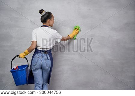 Back View Of Young Housewife Or Maid Woman Uniform And Yellow Rubber Gloves Holding Bucket Or Basket