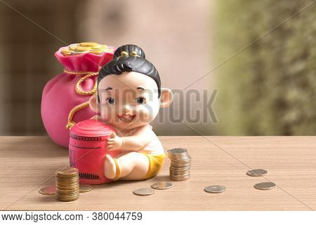 Money Bag And Thai Girl Child Style Of Piggy Bank With Coins On The Wooden Table And Blurred Backgro