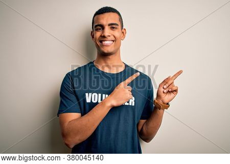 Young handsome african american man volunteering wearing t-shirt with volunteer message smiling and looking at the camera pointing with two hands and fingers to the side.