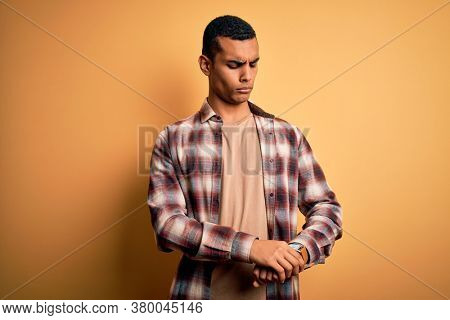 Young handsome african american man wearing casual shirt standing over yellow background Checking the time on wrist watch, relaxed and confident