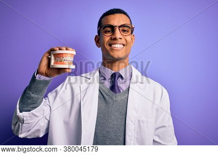 Young handsome african american dentist man holding denture teeth with dental braces with a happy face standing and smiling with a confident smile showing teeth