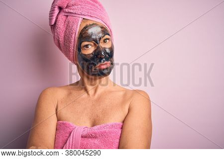 Middle age brunette woman wearing beauty black face mask over isolated pink background skeptic and nervous, disapproving expression on face with crossed arms. Negative person.