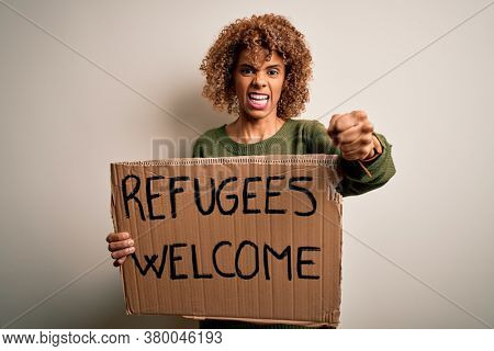 African american woman asking for immigration holding banner with wlecome refugees message annoyed and frustrated shouting with anger, crazy and yelling with raised hand, anger concept