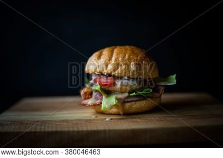 Fresh Tasty Burger On Black Background. Delicious Fresh Homemade Burger On A Wooden Table