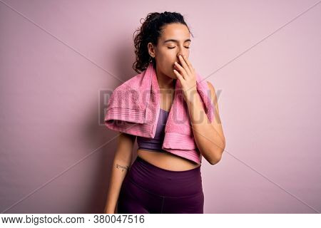 Young beautiful sportswoman with curly hair doing sport using towel over pink background bored yawning tired covering mouth with hand. Restless and sleepiness.