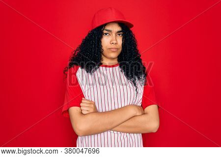 Young african american curly sportswoman wearing baseball cap and striped t-shirt skeptic and nervous, disapproving expression on face with crossed arms. Negative person.