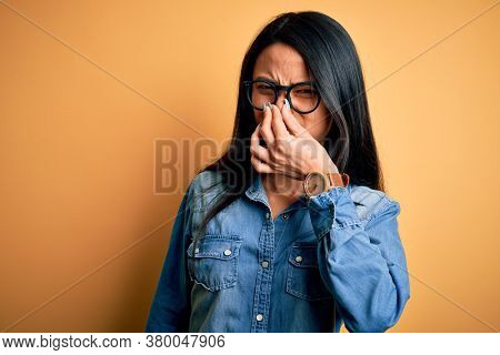 Young beautiful chinese woman wearing casual denim shirt over isolated yellow background smelling something stinky and disgusting, intolerable smell, holding breath with fingers on nose. Bad smell