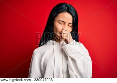 Young beautiful chinese sporty woman wearing sweatshirt over isolated red background feeling unwell and coughing as symptom for cold or bronchitis. Health care concept.
