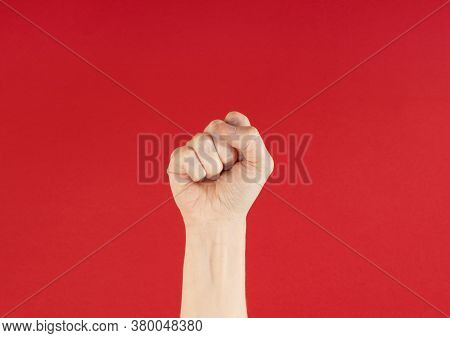 Raised Fist In Front Of A Red Background, With Copy Space