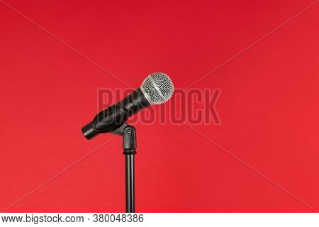 Microphone And Stand, Isolated Against A Bright Red Background, With Copy Space