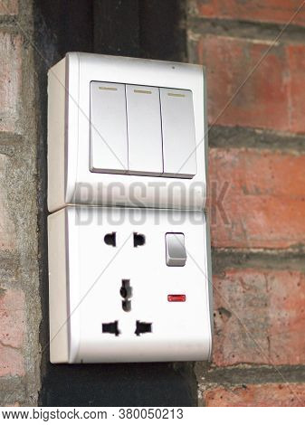 Three-key Switch Gray On The Wall A Plastic Mechanical Switch. The Concept Of Energy Savings. Closeu