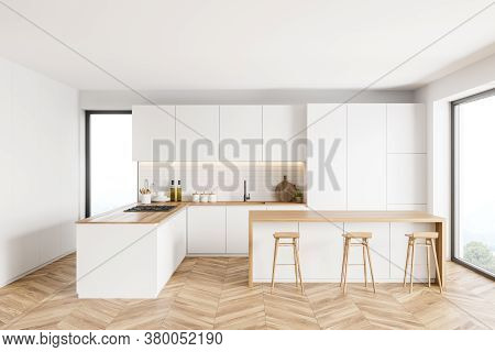 Interior Of Modern Kitchen With White And Brick Walls, Wooden Floor, White Cupboards And Bar With St