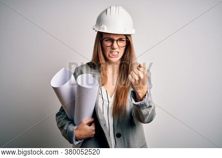 Young beautiful redhead architect woman wearing glasses and safety helmet holding blueprints annoyed and frustrated shouting with anger, crazy and yelling with raised hand, anger concept