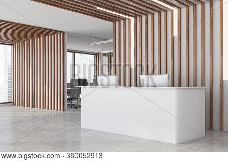 Corner Of Modern Office Waiting Room With Wooden Walls, Concrete Floor And White Reception Desk. Ope