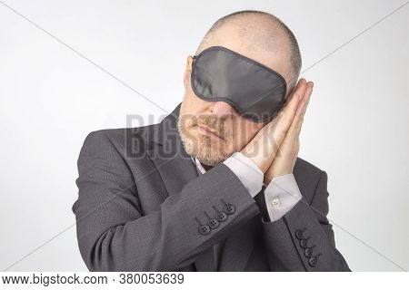 Business Man In Blindfold For Sleeping With Arms Raised For Rest On A White Background