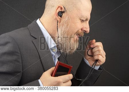 Bearded Business Man Likes To Listen To His Favorite Music At Home With An Audio Player In Small Hea