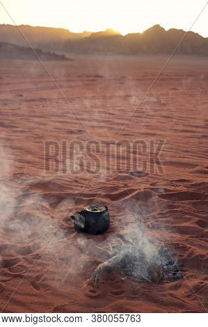Old Kettle Is Boiling On An Open Air In A Sand Bedouin Wadi Rum Desert In Jordan