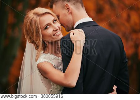 Portrait Of Happy Young Married Couple In Golden Yellow Fall Autumn Park. Beautiful Bride And Stylis