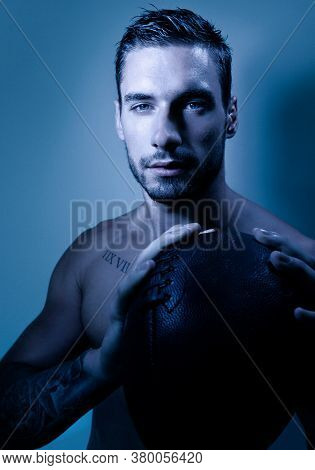 Portrait Of Young Attractive Topless Muscular Man With Beard Holding American Football And Looking A