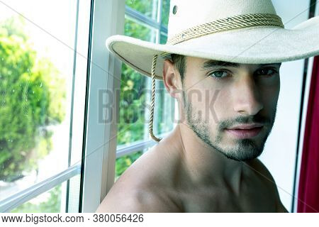 Portrait Of Handsome Muscular Cowboy Sitting In Window Looking At Camera