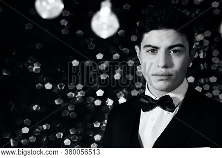 Good Looking Man In Tuxedo Standing Under String Lights With Bokeh Blurred Lights In The Background