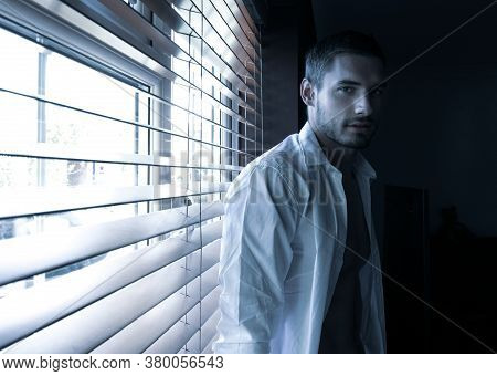 Portrait Of Handsome Man With Beard Standing Next To Window With Open Shirt And Defined Pecs