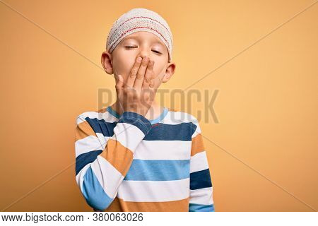Young little caucasian kid injured wearing medical bandage on head over yellow background bored yawning tired covering mouth with hand. Restless and sleepiness.