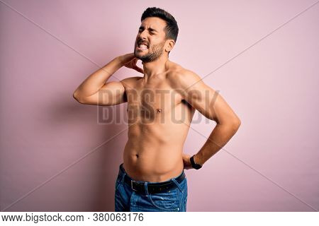 Young handsome strong man with beard shirtless standing over isolated pink background Suffering of neck ache injury, touching neck with hand, muscular pain