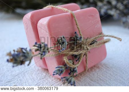 Two Bars Of Pink Handmade Soap Tied With Twine And Lavender Flowers On The White Wooden Background.