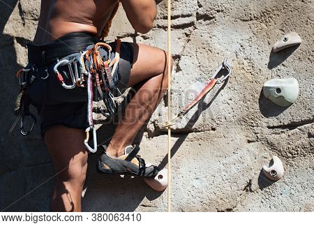 Sportsman Climber Moving Up On Steep Rock, Climbing On Artificial Wall Outdoors. Extreme Sports And