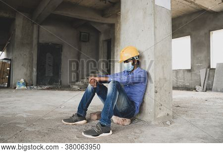 Construction Worker Sitting Sad And Lonely At Job Site Wearing A Medical Mask With Hardhat To Preven