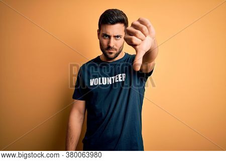Young handsome man with beard volunteering wearing t-shirt with volunteer message with angry face, negative sign showing dislike with thumbs down, rejection concept