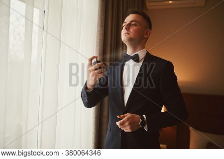 Morning Of The Groom Before The Wedding. Groom Morning Preparation. Young And Handsome Groom Sprayin