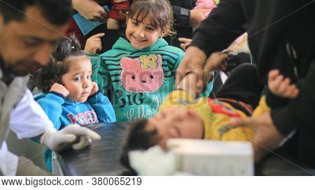 Aleppo, Syria, December 21, 2019 A Cute Baby Girl Smiles Upon Seeing Her Little Brother Crying Durin