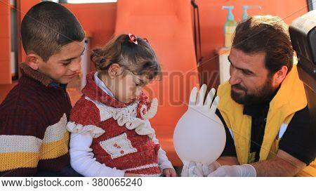 Aleppo, Syria, December 21, 2019 A nurse tries to make a sick child laugh