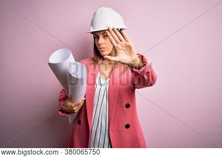 Young beautiful brunette architect woman wearing safety helmet holding blueprints with open hand doing stop sign with serious and confident expression, defense gesture