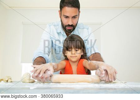 Focused Girl And Her Dad Kneading And Rolling Dough On Kitchen Table With Flour Messy. Father Teachi